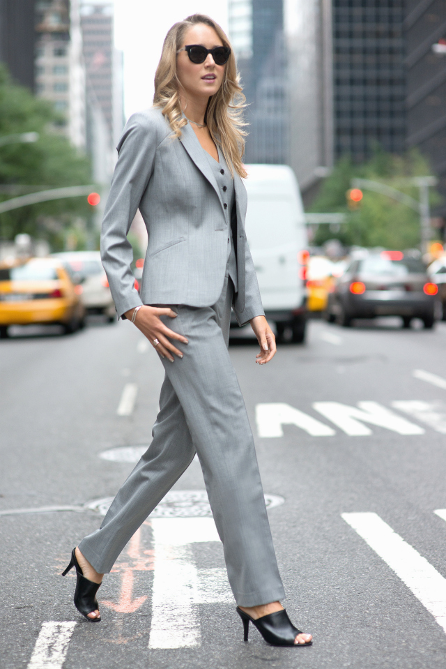 professional woman wearing leather black mules and a grey suit
