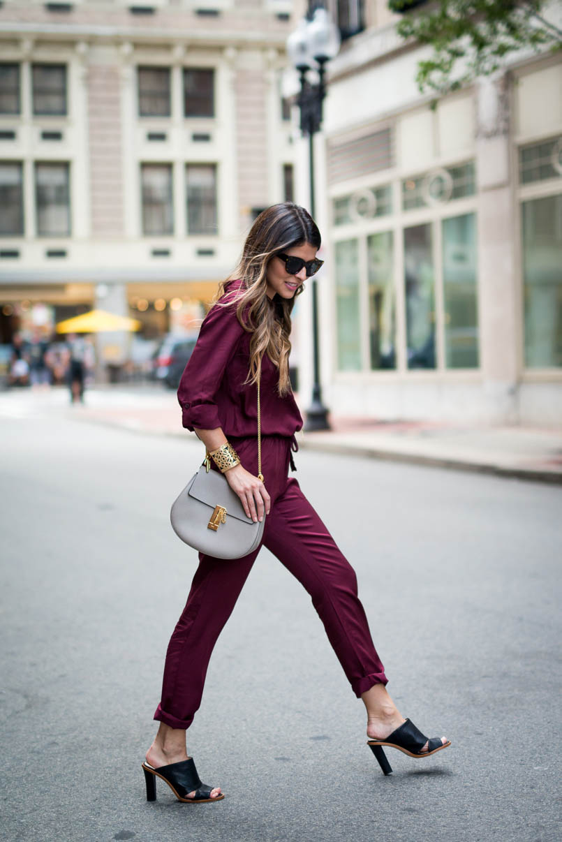 woman wearing a burgundy satin jumpsuit with black leather cutout mules